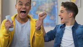 Dwa męskiego szkoła średnia przyjaciela ogląda sporta dopasowanie na tv, mistrzostwo drużyna wachlują zbiory
