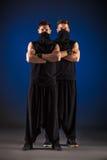 Dwa męskiego tancerza pozuje w ninja kostiumach przeciw błękitnemu backgroun Obraz Stock