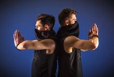 Dwa męskiego tancerza pozuje w ninja kostiumach przeciw błękitnemu backgroun Zdjęcia Royalty Free