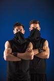 Dwa męskiego tancerza pozuje w ninja kostiumach przeciw błękitnemu backgroun Zdjęcie Stock