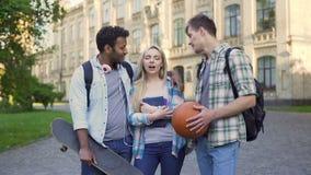 Dwa męskiego ucznia flirtuje z piękną blond dziewczyną blisko uniwersyteta, żartuje zdjęcie wideo