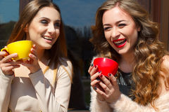 Dwa młoda ładna kobieta śmia się outdoors i pije kawę Li Obrazy Royalty Free