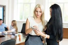 Dwa młoda biznesowa kobieta z pastylka komputerem w biurze d Obrazy Stock