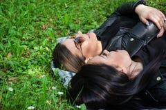 Dwa młoda dziewczyna łgarskiego puszka na koc i opowiadać w zielonej łące na wiosna dniu w naturze fotografia stock