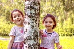 Dwa młoda dziewczyna stojaka blisko drzewa fotografia stock