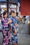 Dwa młoda kobieta jest ubranym japońskiego tradycyjnego kimono cieszy się przespacerowanie obrazy stock