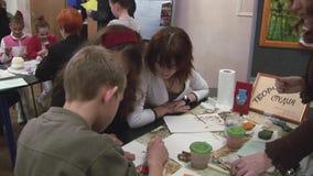 Dwa młoda kobieta pomaga nastoletniej chłopiec rysować bawełnianym mopem przy stołem festiwale tworzenie Ręcznie Robiony zdjęcie wideo