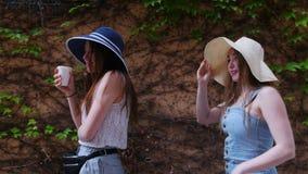 Dwa młoda kobieta przyjaciela chodzi w panamas na ulicach i opowiada - jeden one pije napój od filiżanki zbiory