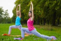 Dwa młoda kobieta robi gimnastycznym ćwiczeniom plenerowym Zdjęcie Stock