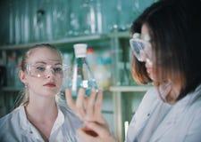 Dwa młoda kobieta w chemicznym lab trzymający kolby z jasnym cieczem w nim Blondynki kobieta w ostrości zdjęcie stock