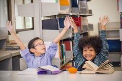 Dwa młode dziecko czytelniczej książki przy szkolną biblioteką Fotografia Stock