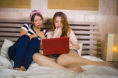 Dwa młodego ładnego i szczęśliwych Azjatyckiego Chińskiego studenckiego dziewczyny sypialni dopatrywania interneta Koreańskiego d zdjęcie royalty free