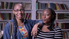 Dwa młodego amerykanina afrykańskiego pochodzenia żeńskiego przyjaciela stoi w bibliotecznym i ono uśmiecha się przy kamerą, półk zbiory