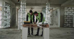 Dwa młodego architekta robi praca planowi dla budowy zbiory
