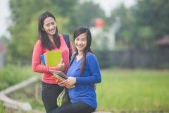Dwa młodego Azjatyckiego ucznia trzyma książki, ono uśmiecha się jaskrawy fotografia stock