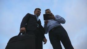 Dwa młodego biznesmena opowiada pastylka komputeru osobistego plenerowego pożegnanie i używa wtedy i różnią się Biznesowi mężczyz Zdjęcie Royalty Free