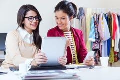 Dwa młodego bizneswomanu pracuje z cyfrową pastylką w ona offic Zdjęcia Stock