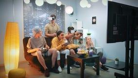 Dwa młodego człowieka bawić się konsoli grę w rzeczywistość wirtualna szkłach wśród rozochoconej firmy zdjęcie wideo