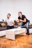 Dwa młodego człowieka ogląda sport rywalizację i pije piwo na tv Zdjęcia Stock