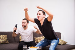 Dwa młodego człowieka ogląda sport rywalizację i pije piwo na tv Zdjęcie Royalty Free
