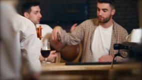 Dwa młodego człowieka przyjaciela siedzi w prętowym i opowiada z each inny podczas gdy pijący piwo zbiory