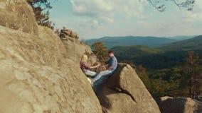 Dwa młodego kochanka siedzą na wierzchołku skała w górach i trzymają ich ręki Para cele być szczęśliwym zdjęcie wideo