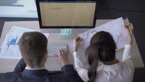 Dwa młodego ludzie biznesu pracują na projekcie, siedzący przy stołem z pecetem, patrzejący, czytający dokument, dzieli pomysły zbiory