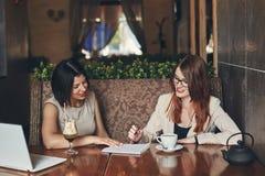 Dwa młodego one uśmiechają się caucasian bizneswomanu z laptopem Kobiety w kawiarni Zdjęcie Stock