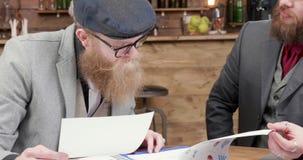 Dwa młodego partnera biznesowego patrzeje nad diagramami brać cieżkie decyzje próbą i zdjęcie wideo