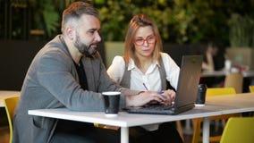 Dwa młodego profesjonalisty siedzi przy biurkiem, patrzeje laptopu ekran i dyskutuje projekt wpólnie, M??czyzna i kobiety dzia? zdjęcie wideo