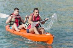 Dwa młodego przyjaciela ejoying wakacje, iść w morzu z koloru żółtego czółnem fotografia royalty free