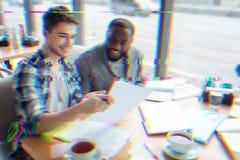 Dwa młodego specjalisty ono uśmiecha się podczas gdy pracujący z dokumentami zdjęcie stock