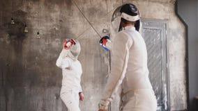 Dwa młodego szermierza ćwiczą lunges i ataki z sabers w ciemnej sala zdjęcie wideo