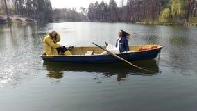 Dwa młodej ładnej dziewczyny siedzi w małej łódce po środku pięknego odbijającego jeziora lub rzeki aktywny tryb ?ycia zbiory wideo