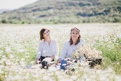 Dwa młodej ładnej kobiety ma pinkin z herbatą w chamomile polu Obraz Royalty Free