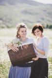 Dwa młodej ładnej kobiety pozuje w chamomile polu Zdjęcie Stock
