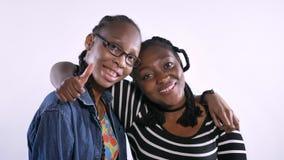 Dwa młodej amerykanin afrykańskiego pochodzenia kobiety ściska i ono uśmiecha się przy kamerą, szczęśliwy, odosobniony nadmierny  zdjęcie wideo