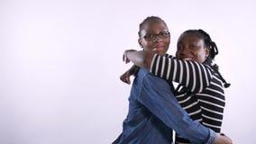 Dwa młodej amerykanin afrykańskiego pochodzenia kobiety ściska i patrzeje kamerę odizolowywającej na białym tle, szczęśliwej, cza zdjęcie wideo