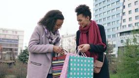 Dwa młodej amerykanin afrykańskiego pochodzenia kobiety dzieli ich nowych zakupy w shoppping zdosą z each inny Atrakcyjny dziewcz zdjęcie wideo