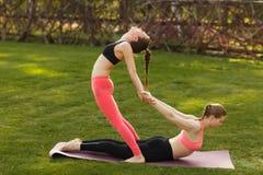Dwa młodej atrakcyjnej dziewczyny ćwiczy joga plenerowy Fotografia Stock