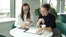 Dwa młodej biznesowej dziewczyny z szkłami przychodzili jeść lunch w kawiarni pić kawę i dyskutować biznes zbiory