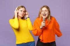 Dwa młodej blondynka bliźniaków siostr dziewczyny w kolorowych ubraniach słuchają muzykę z hełmofonami, śpiewają piosenkę w mikro obraz royalty free