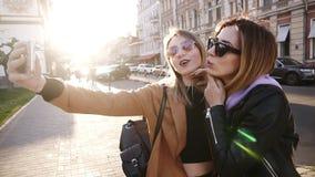 Dwa młodej caucasian mody kobiety w okularach przeciwsłonecznych pozuje dla selfie i śmia się z tonque Styl życia portret na ulic zdjęcie wideo
