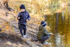 Dwa młodej chłopiec bawić się połów z kijami blisko stawu w spadku parku Młodsi bracia ma zabawę blisko jeziora lub rzeki w jesie Zdjęcie Stock