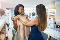 Dwa młodej damy robi zakupy dla odziewają zdjęcie stock