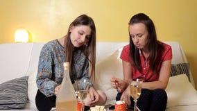 Dwa młodej dziewczyny pije gronowego wino i je siedzą na leżance w domu tort i gawędzić Przyjaźń, cukierki zbiory wideo