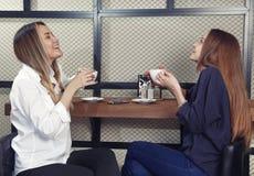 Dwa młodej dziewczyny są szczęśliwi i roześmiani podczas gdy pijący herbaty przy kontuarem w kawiarni Obrazy Stock