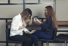 Dwa młodej dziewczyny są szczęśliwi i roześmiani przy kontuarem w kawiarni podczas gdy jeden patrzeć w smartphone Obraz Stock