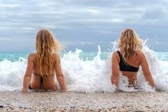 Dwa młodej dziewczyny siedzi w kipieli fotografia stock