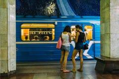Dwa młodej dziewczyny stoi na staci metru na tle jazda pociąg Zdjęcie Stock